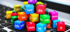 Creative abstract global internet communication PC technology and web telecommunication business computer concept: macro view of group of color cubes with domain names on laptop or notebook keyboard with selective focus effect